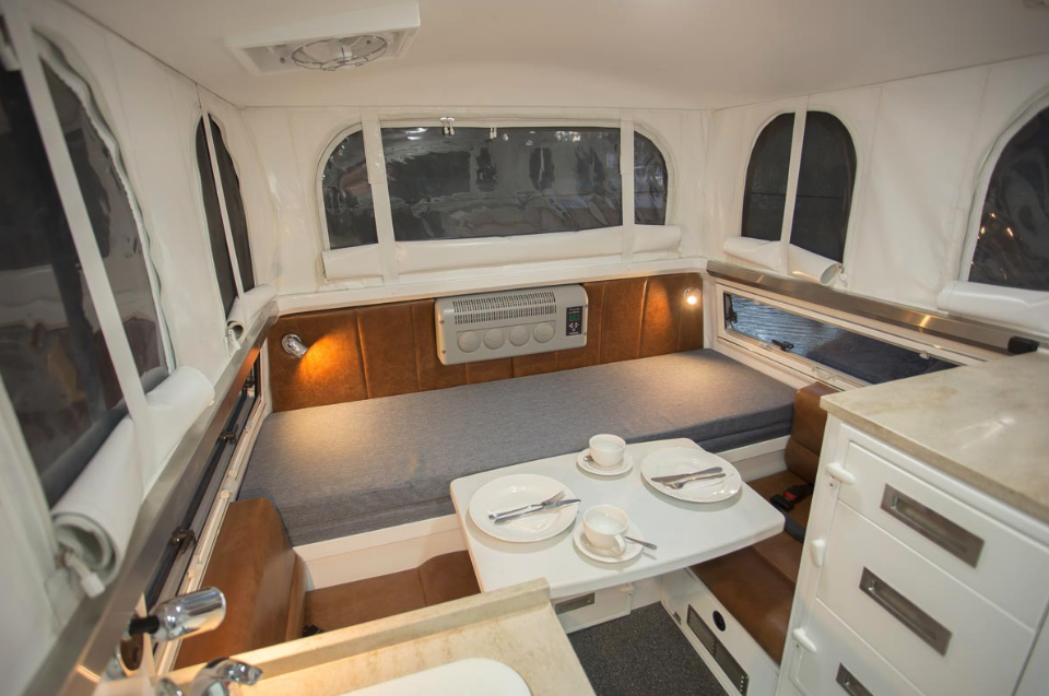 The EarthCruiser Escape features a full camper interior with wet bath, kitchen and convertible dinette/bed