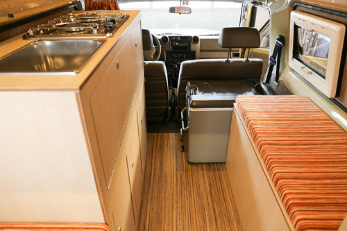 Closer look at Desert-Tec Land Cruiser interior with dual-burner stove, sink, fridge, seating and storage