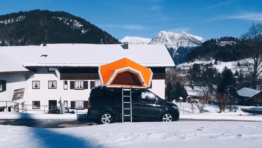 Fjordsen's bright-orange tent stands out against the snowy backdrop