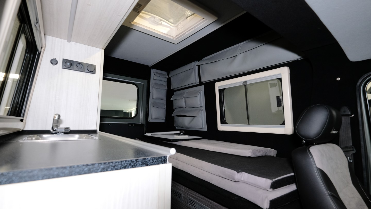 The camper conversion includes a convertible sofa-bed, kitchen counter with sink and storage