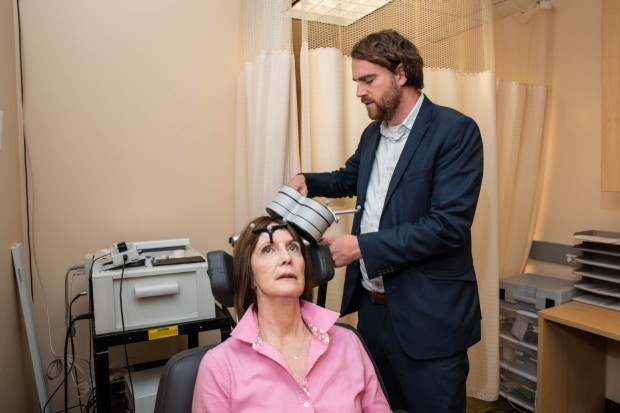 Nolan Williams, senior author on the new study, demonstrating the SAINT treatment with Deirdre Lehman, a subject from the preliminary trial