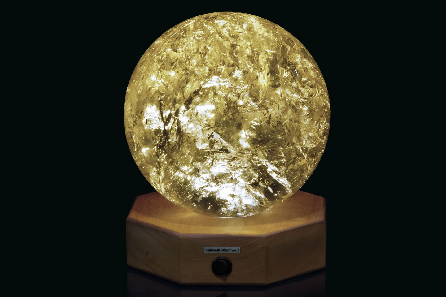 This 81⁄2 inch (21.5 cm) diameter spherical Citrine sample from Brazil has been polished to reveal areas of rainbow iridescence. The specimen is mounted on a wood base with lighting for the specimen from below.