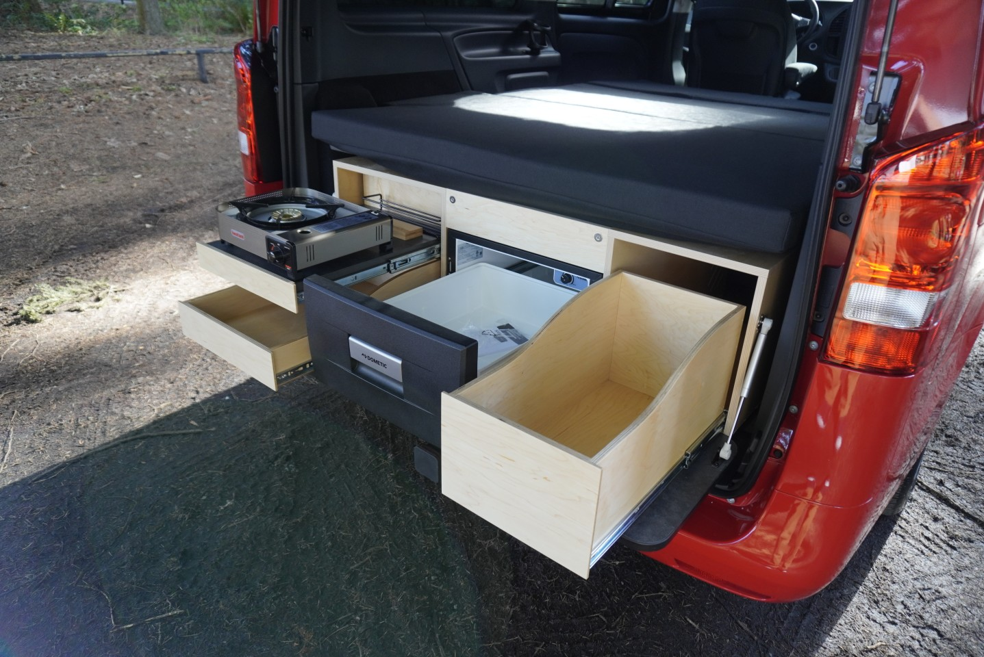 The compact kitchen doesn't have a sink, but Caravan Outfitter offers an optional swing-out indoor/outdoor sink unit in front of the rear bench