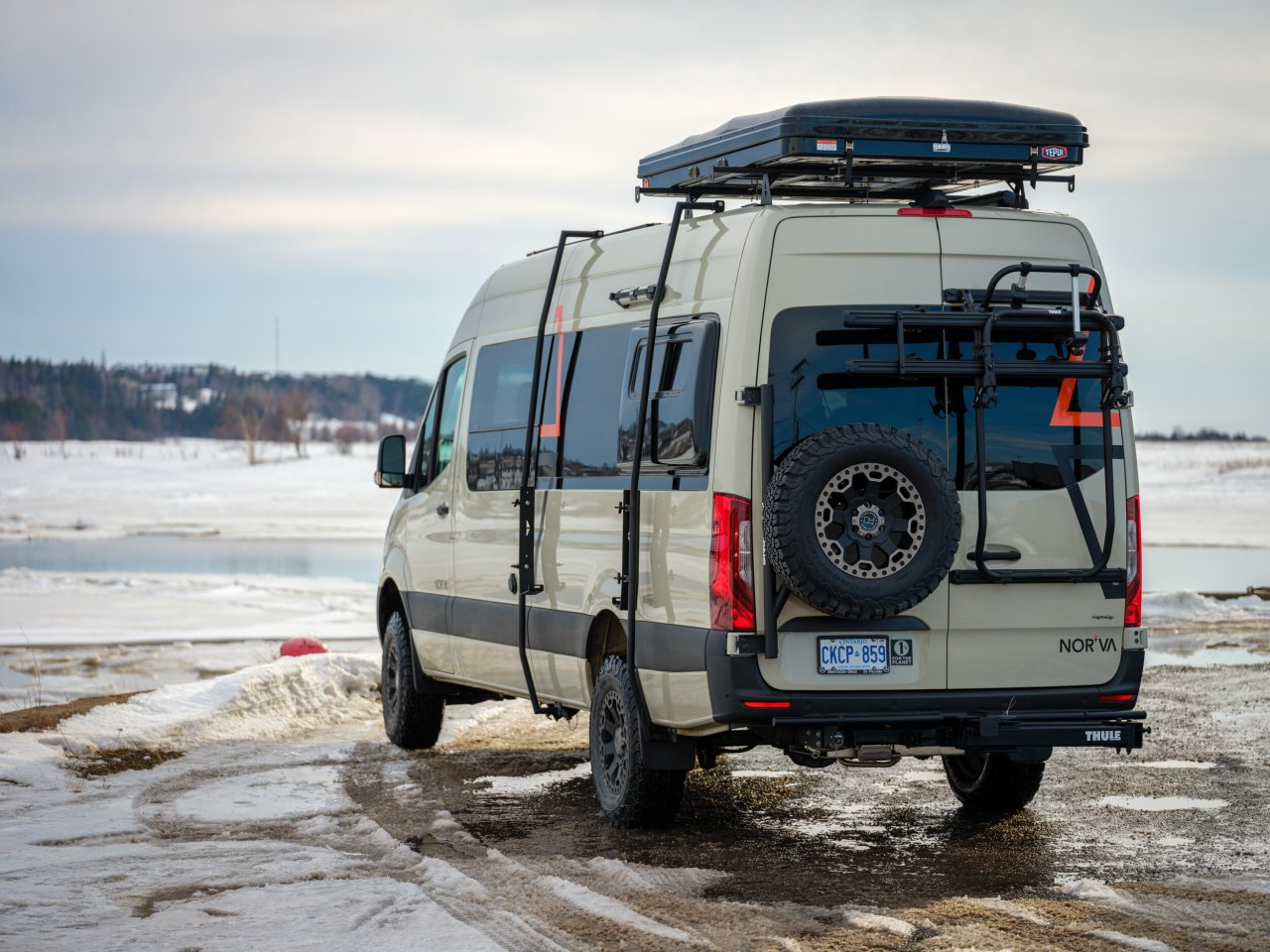 The rear of the camper van has a load door bike rack, a hitch rack and an Owl Vans spare tire carrier