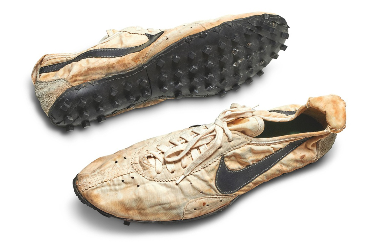 """One of the most significant artefacts in the history of both the Nike brand and sporting culture, this is the Nike """"Moon Shoe"""". It is one of only a handful of pairs known to exist, of the original handmade running shoe designed by Nike co-founder and Oregon University track coach Bill Bowerman. As the famous story goes, Bowerman was first inspired to create the innovative waffle sole traction pattern found on the brand's early running shoes by tinkering with his wife's waffle iron, pouring rubber into the mold to create the first prototype of the sole. The finished design of the traction pattern created better grip and cushion than most running shoes of the time, and the waffle sole was Nike's first major innovation as a brand. The shoes sold for a world record $437,500 in 2019."""