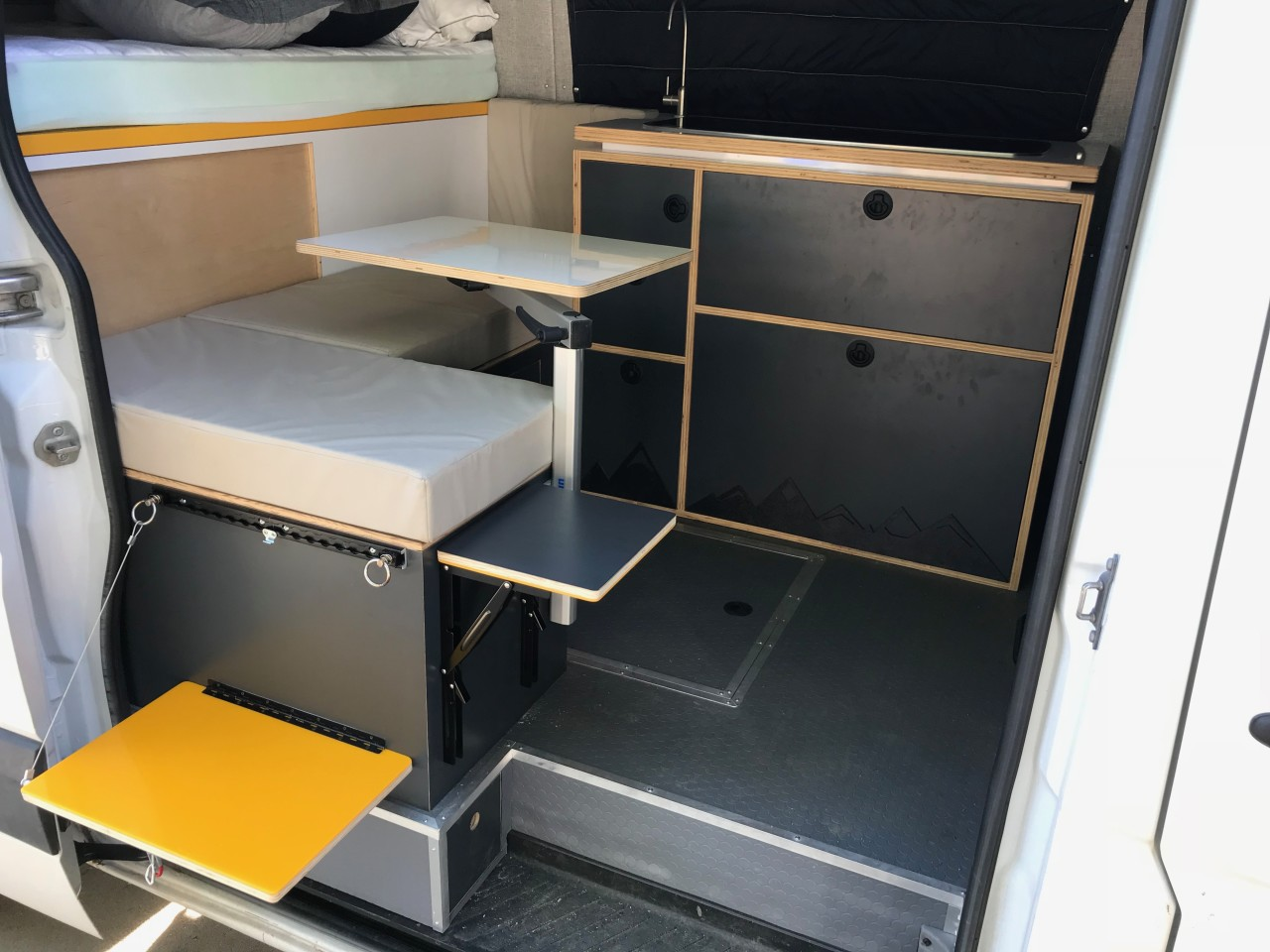 The fold-down yellow table offers a place to put your drink or do some outdoor cooking, while the flip-up gray top inside the doorway serves as a footrest