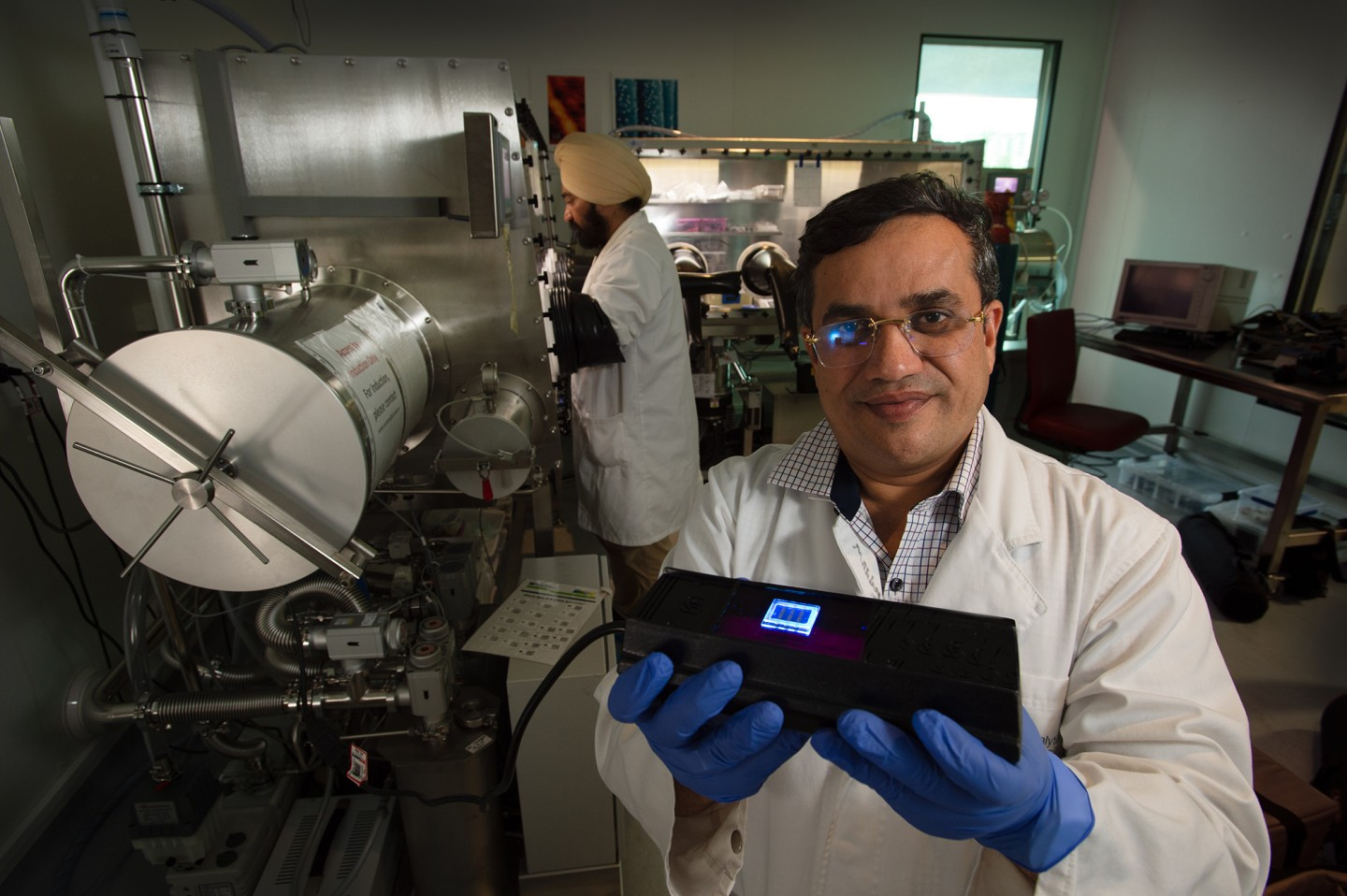 Researchers Prashant Sonar and Amandeep Singh Pannu with their nanodot OLED device
