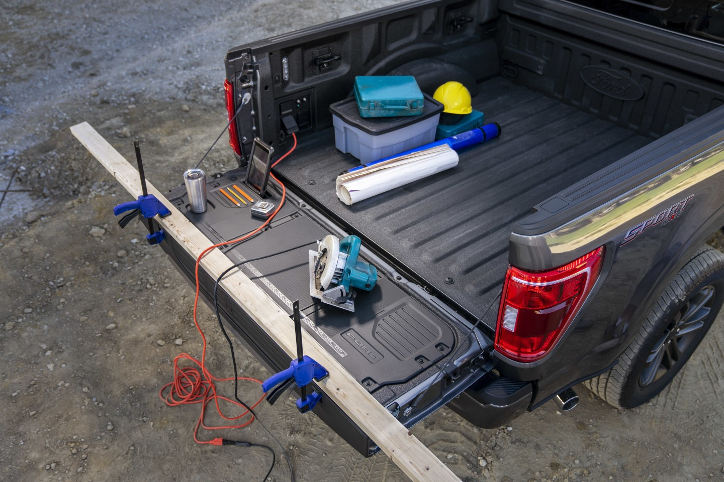 Optional Tailgate Work Surface including integrated rulers, a mobile device holder, cupholder and pencil holder, tie-down cleats (doubling as bottle openers), clamp pockets and optional power generator