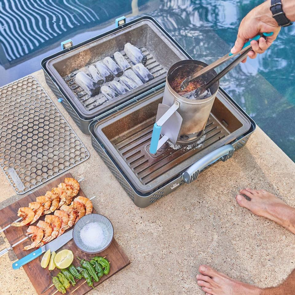Folded open, the Nomad Grill and Smoker features two empty beds that can be filled with charcoal