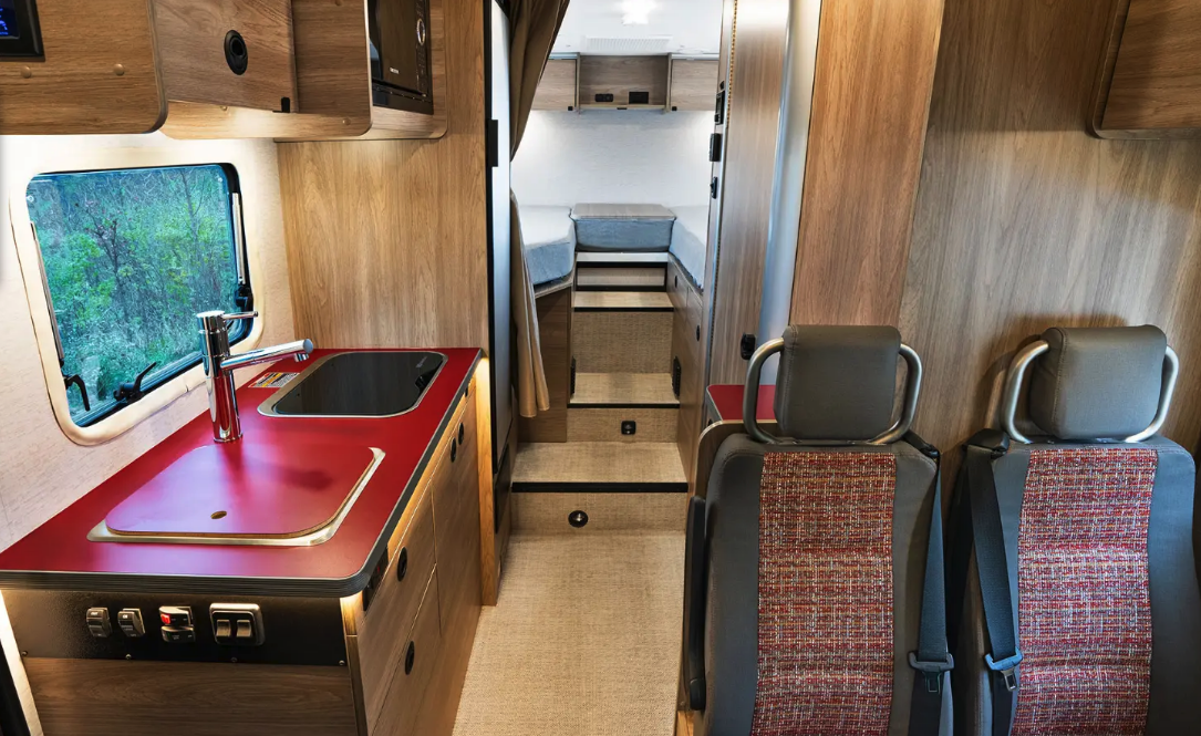 The interior layout is quite familiar from countless European camper vans and small motorhomes, furnished with a driver-side dinette, central kitchen and wet bath, and rear bedroom