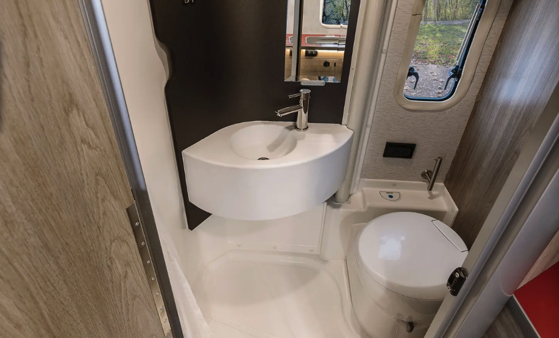 "The clever bathroom uses a swiveling sink wall for ""toilet"" and ""shower"" modes; in toilet mode, the cassette toilet swivels to face the shower, providing the legroom needed to sit down"