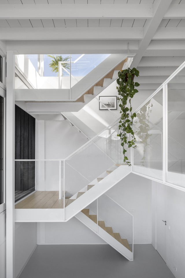 A single zig-zag staircase connects all three levels, which gives rise to cathedral-high ceilings