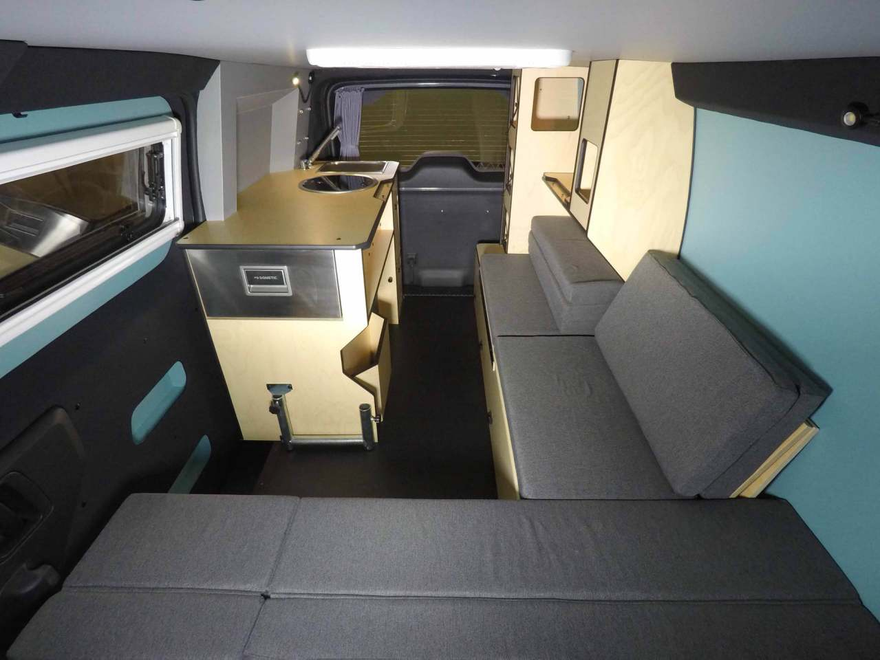 The Mobile Base Camp interior is filled out with an L-shaped sofa, storage shelving and a kitchen block